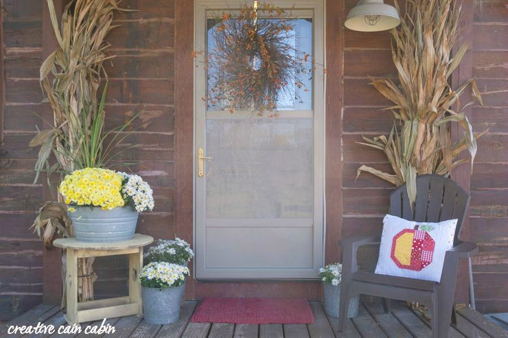 Rustic Fall Porch of a Log Home Using Natural Elements as Decor The Wreath is Made From Weeping Cherry Branches and the Apple Picking PIllow is From the Farm Girl Vintage Book