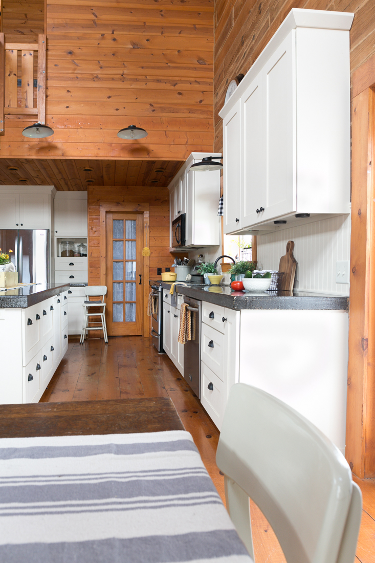 Log Home Kitchen With White Cabinets Beadboard And Black
