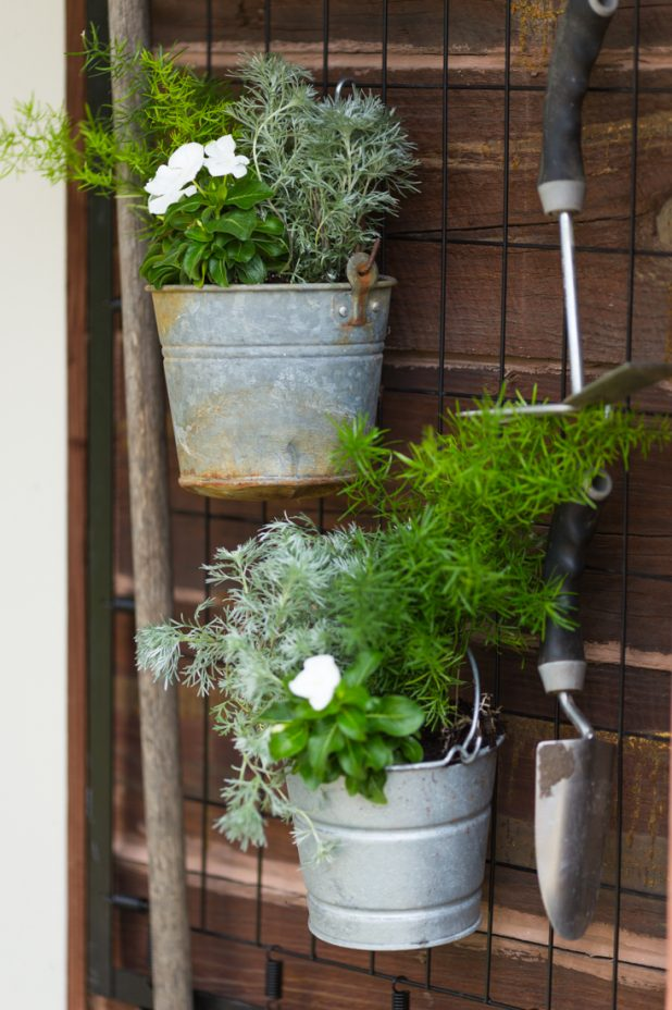 Here's a great way to use that old baby crib. Keep the springs and turn it into hanging garden tool storage. Throw in a few galvanized buckets planted with annuals and it looks like a wall of art. It's the perfect functional rustic look.
