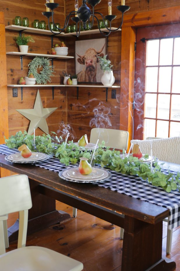 Simple DIY Rustic Thanksgiving Place Setting Using Galvanized Chargers, White Rustic Distressed Dishes, Pears, Thankful and Grateful Place Setting Tags, Silver Dollar Eucalyptus Garland, Spice Jar Glass Bottles, Candles, and a Black and White Checked Table Runner for an Easy To Recreate Farmhouse Look