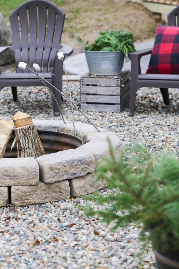 Rustic Christmas Fire Pit Decorated With Pine Clipping and Buffalo Check Fabric