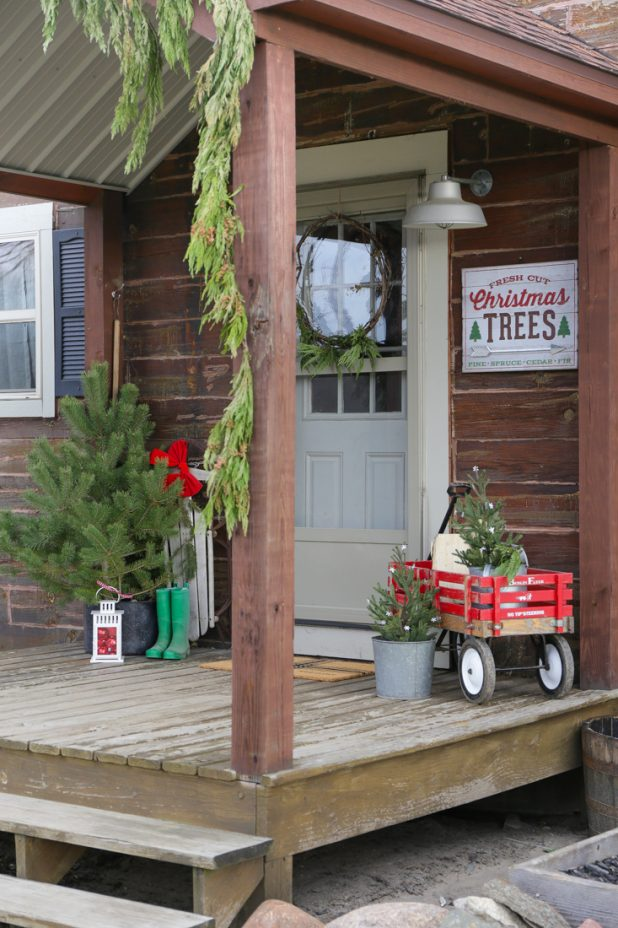Rustic Log Home Christmas Porch, Fresh Cut Pines, Vintage Red Wagon, Grapevine Wreath, Pine Clippings, Boots, and Galvanized Buckets