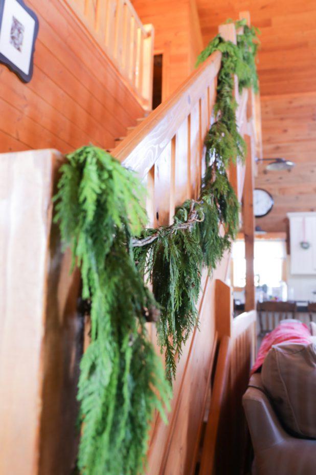 Fresh Christmas Garland on the Railing of a Rustic Log Home