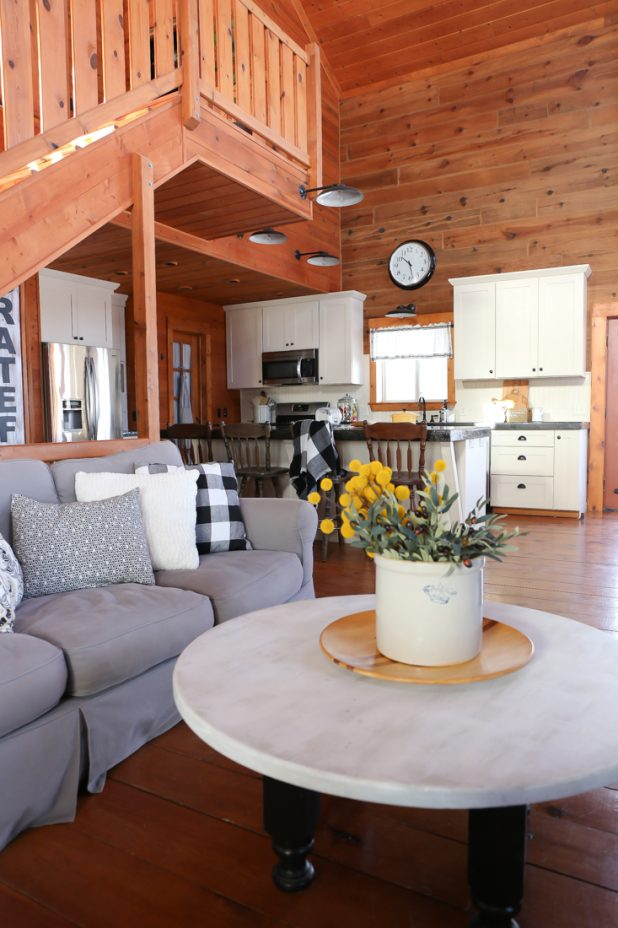 Living Room and Kitchen of a Log Home. White, Black, Gray, and Yellow Decor