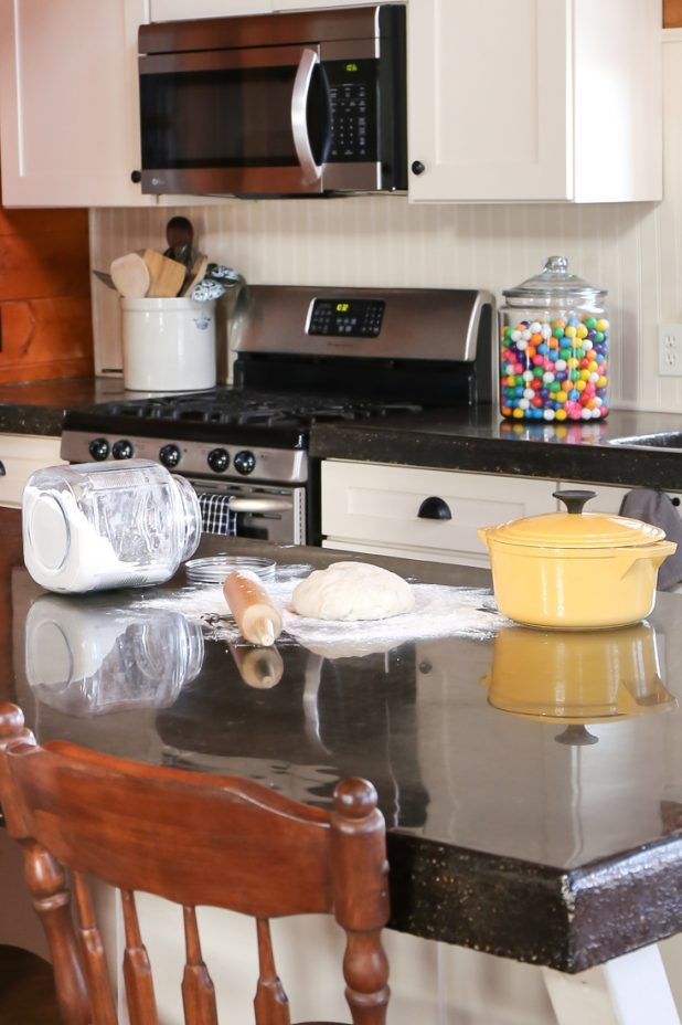 Baking Home Made Bread in a Log Home Kitchen. White Cabinets, Black Concrete Countertop, Yellow Enamelware Dutch Oven, Glass Jar with Bubble Gum