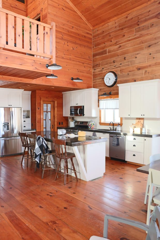 Log Home Kitchen With White Cabinets and Black Concrete Countertops