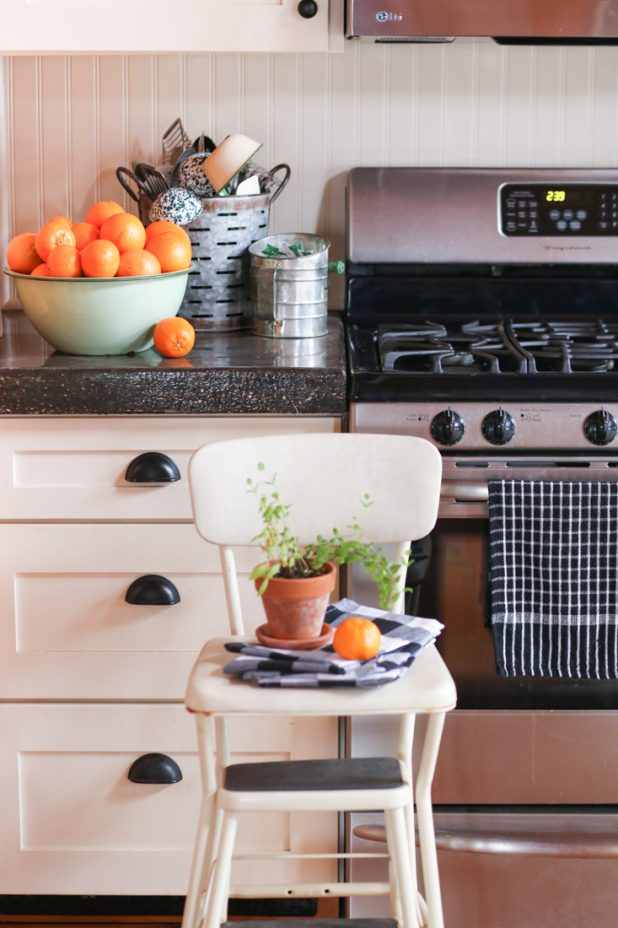 Rustic Country Kitchen Using an Old Olive Bucket For Utensil Storage, and Old Flour Sifter to Store Tea Bags, and Enamelware Bowl for Oranges. Vintage Step Stool, Black and White Buffalo Check Napkins. White Cabinets and Stainless Steel Appliances