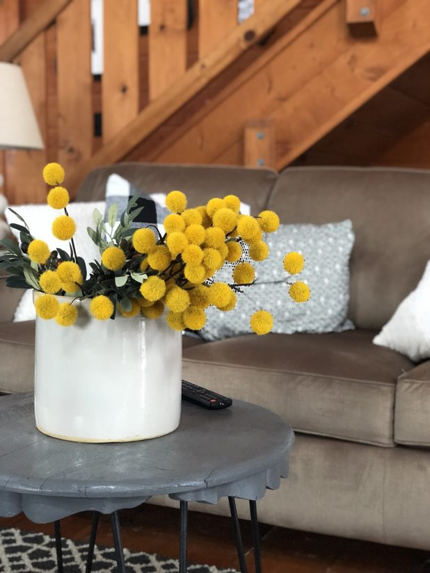Coffee Colored Sofa, Hair Pinned Table, Yellow Flowers in a Crock