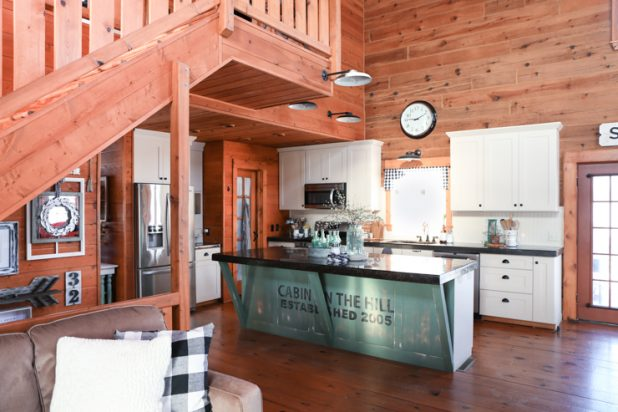 Privilege Green Paint Color on Kitchen Island of a Log Home. Black Concrete Countertops and Upper Cupboard Painted With Sherwin Williams Lotus Pod
