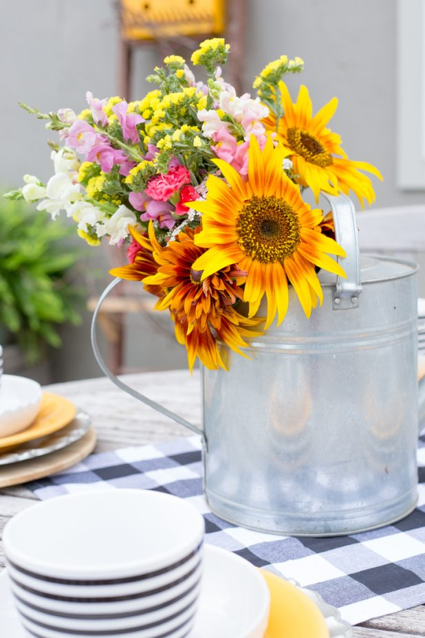 Summer Sunflower Arrangement Outdoors on an African Teak Table Set with Black and White Gingham and Bright Yellow Dishes. Love the Galvanized Watering Can Used as a Flower Vase.