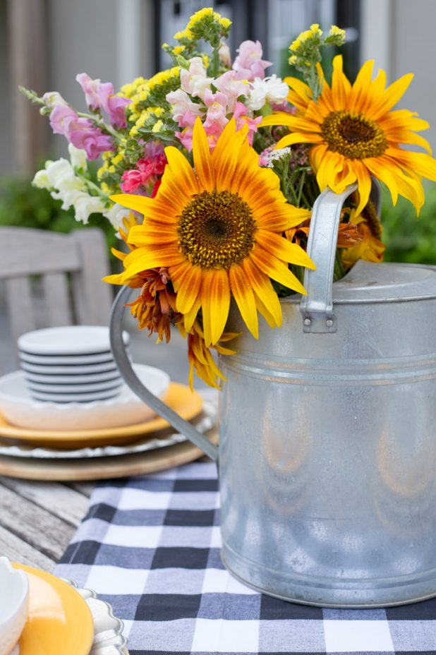 Summer Sunflowers From The Farmers Market Decorate This Outdoor Space, With Touches of Black and White Buffalo Check, Bright Golden Dishes, A Galvanized Watering Can Makes For A Lovely Centerpiece While Dining Al Fresco