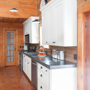 Log Home Kitchen with White Cabinet & Black Concrete Countertops | creativecaincabin.com