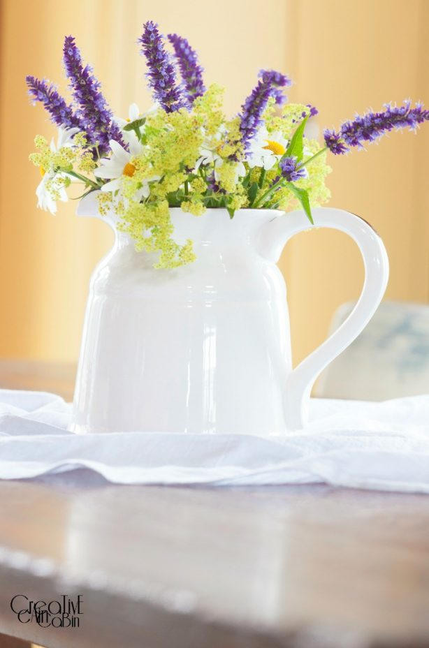 Summer Flower Arrangement Using Daisy's, Black and Blue Salvia, and Cora Bells in an Enamelware Pitcher | CreativeCainCabin.com
