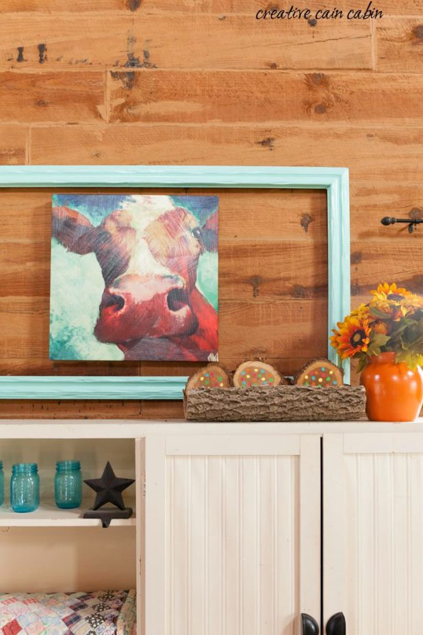 Buy an oversized ugly painting at a garage sale for pennies and turn it into a new piece of art by framing out an existing painting or sculpture