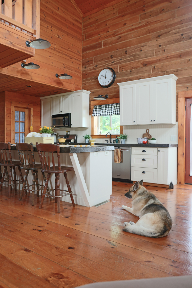 Log Home Kitchen With White Cabinets, Beadboard, and Black Concrete Countertops