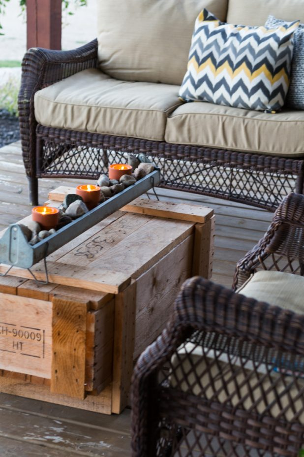 Old Galvanized Chicken Feeder Used as a Candle Holder For a Rustic Look on a Log Home Porch, The Coffee Table is an Old Shipping Crate