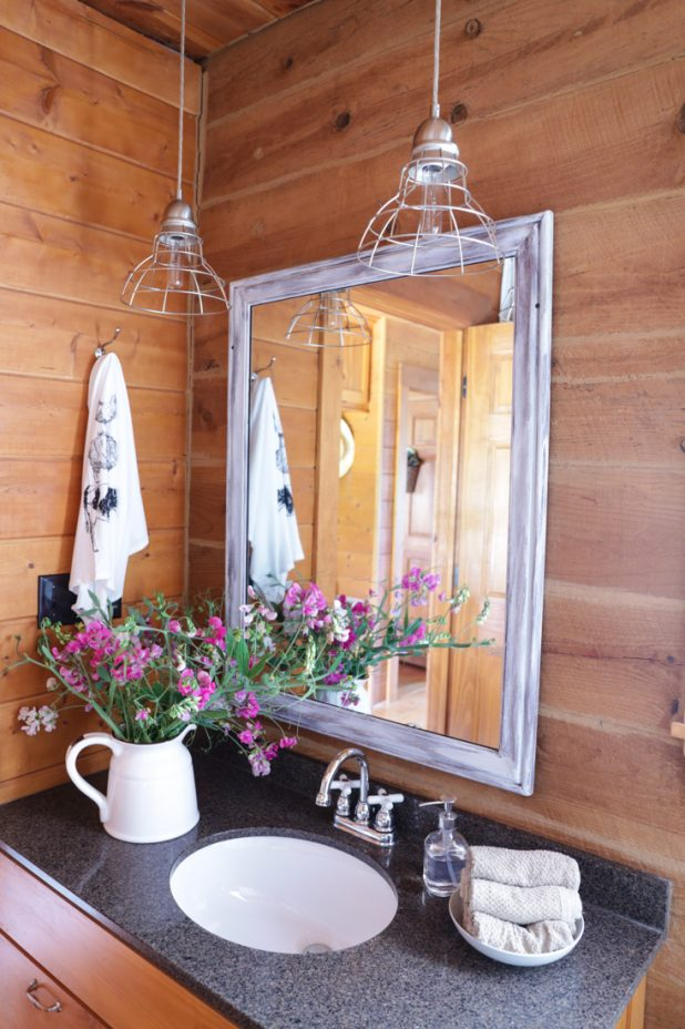 Guest Bath Rustic Farmhouse Makeover with Granite Countertops, Cage Lights, A Transformed Garage Sale Mirror, Enamelware, Wildflowers, With the Washer and Dryer Incorporated Into the Space