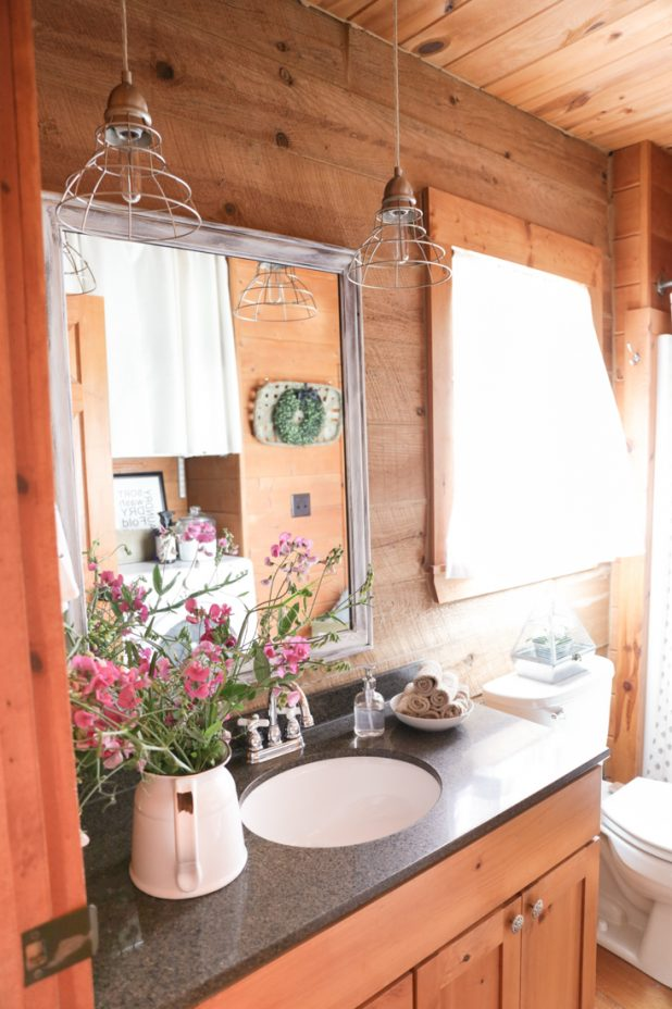 Guest Bath Farmhouse Makeover Using Cage Lights, A Garage Sale Mirror That Was Transformed, Enamelware Vase Filled With Wild Flowers, All Against A Rustic Log Cabin Background