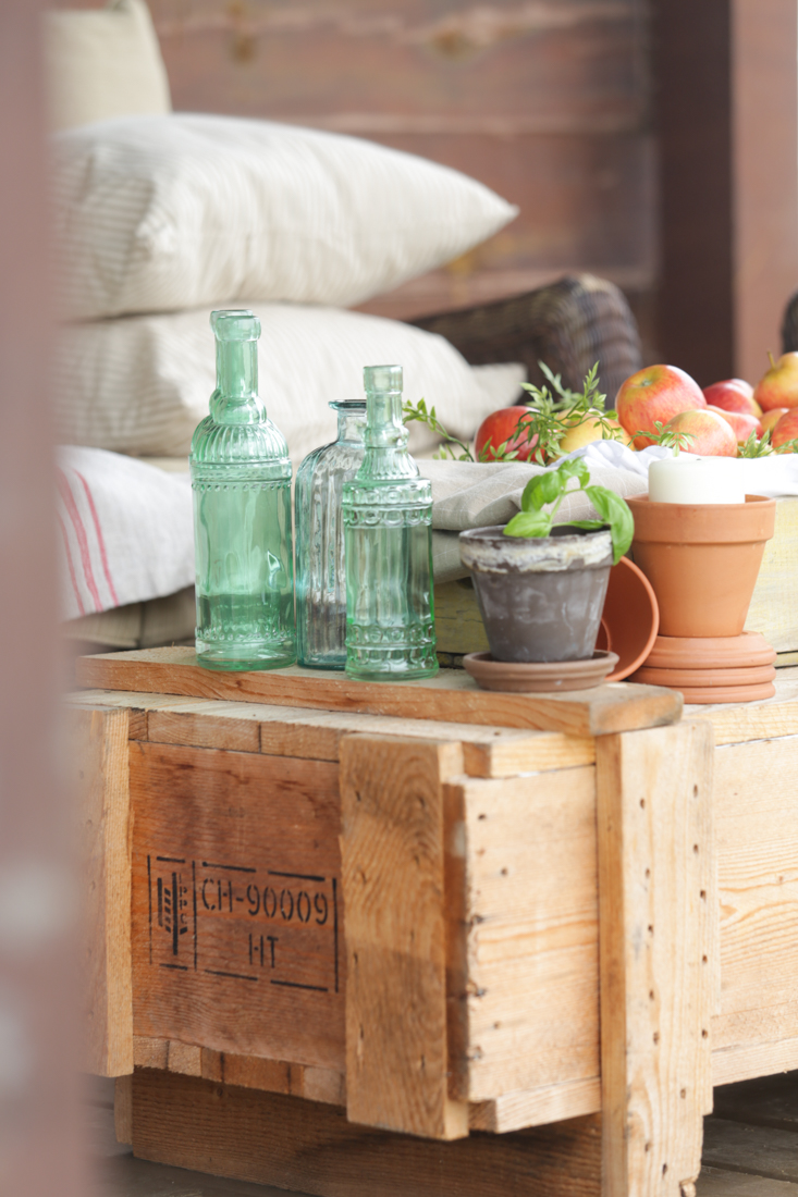 Rustic fall porch decor with apples, a shipping crate, sea glass green bottles, herbs, terra cotta pots, and ticking pillows