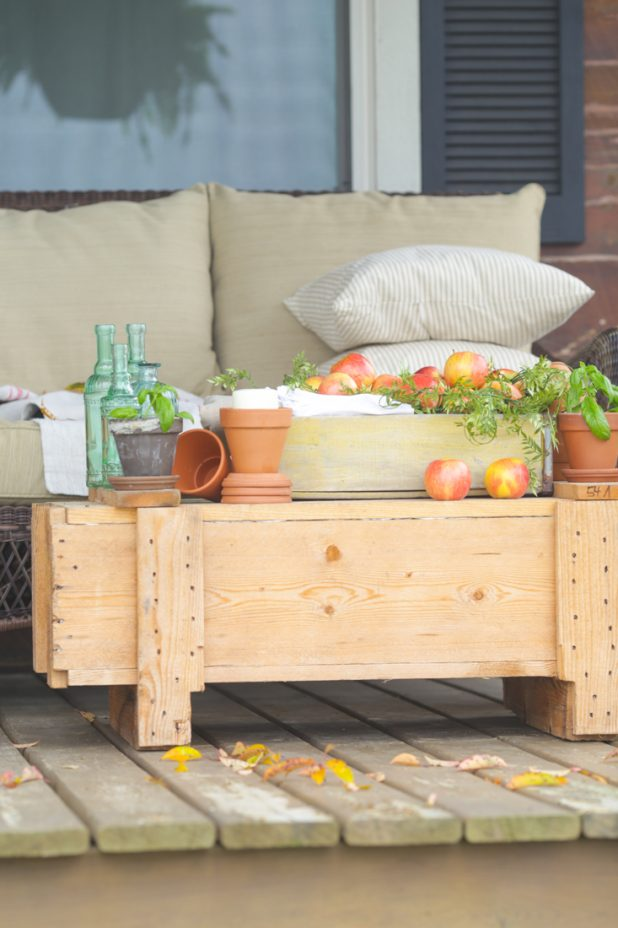Early fall porch decorating using apples, terra cotta pots, herbs, green sea glass bottles, a rustic crate, and ticking pillows