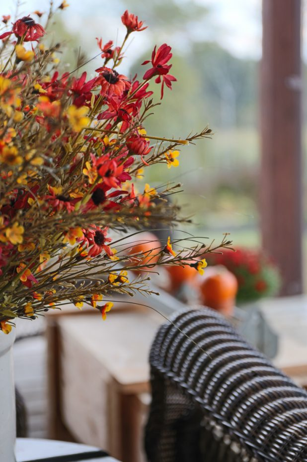 Rustic Fall Porch of a Log Home Decorated With Mums and Pumpkins