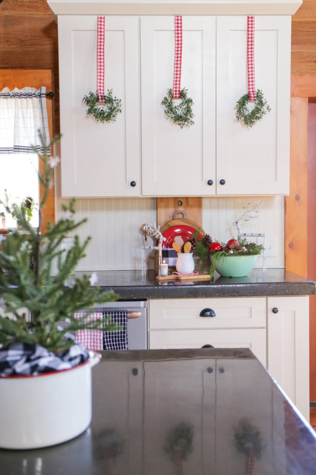 Vintage Enamelware Christmas Kitchen Decor, White Cupboards, Black Concrete Countertops, Vintage Enamelware, Cutting Boards, Wooden Spoons, and Red Dinnerware