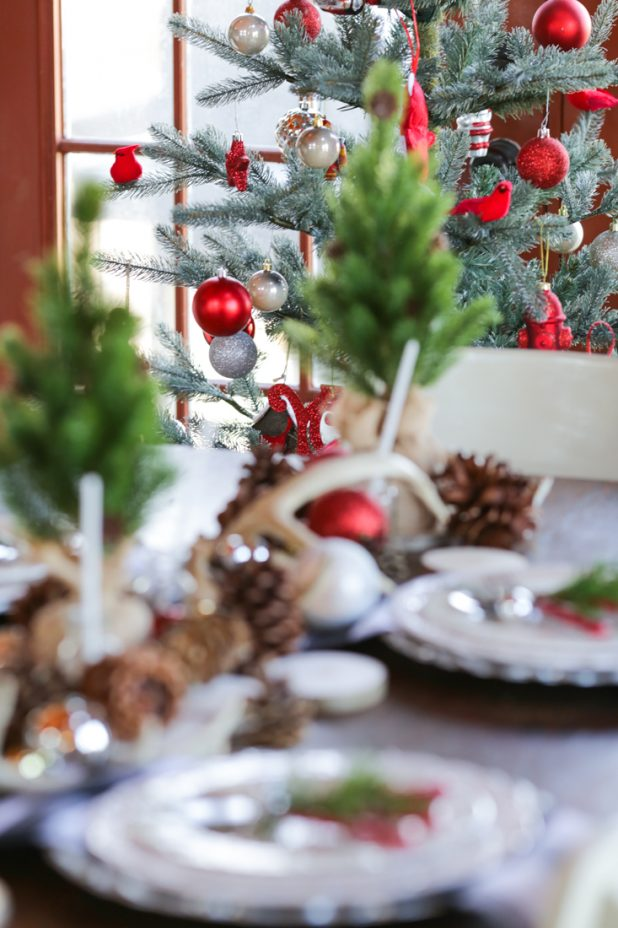 Rustic Christmas Dining Room in a Log Home. Traditional Red and White Christmas using Pinecones, Deer Antlers, and Greenery