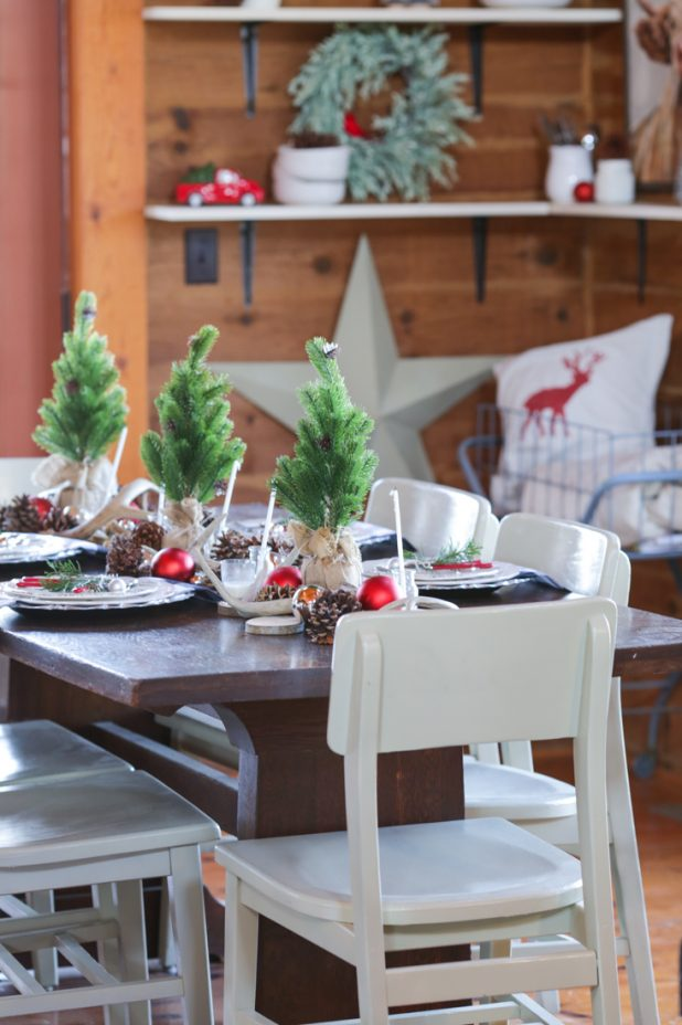 Rustic Christmas Dining Room in a Log Home. Traditional Red and White Christmas using Pinecones, Deer Antlers, Black and White Buffalo Check Fabric, and Greenery