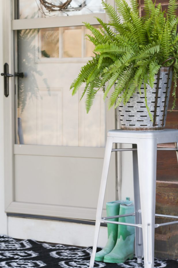 Farmhouse porch decor using olive buckets, Boston ferns, Galvanized stools, and a reversible black and white outdoor rug