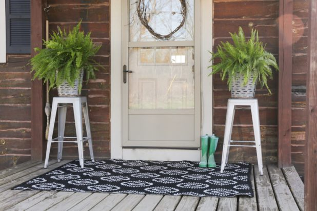 Rustic Log Home With a Farmhouse Decor Porch Theme, Olive Buckets, a Handmade Grapevine Wreath, Galvanized Stools, and a Black and White Reversible Outdoor Rug
