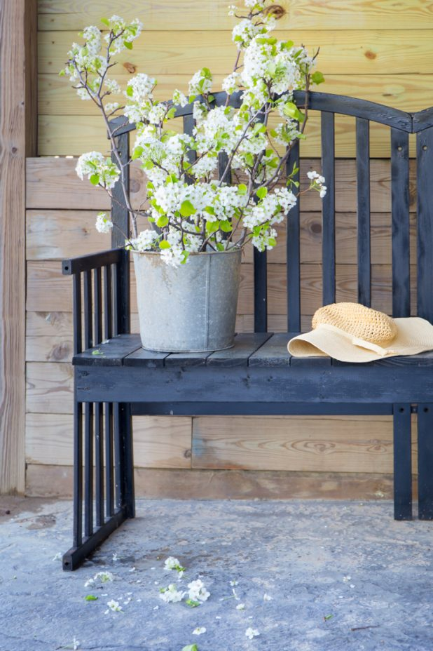 Decorating with flowering pear branches, a galvanized sap bucket, and a DIY garden bench from an old baby crib