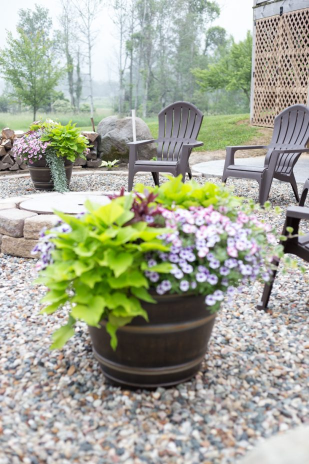 Outdoor Summer Fire Pit Area With Adirondack Chairs, Barrels of Annual Flowers, Stamped Concrete, Large Stones, Retainer Wall at a Log Cabin Home