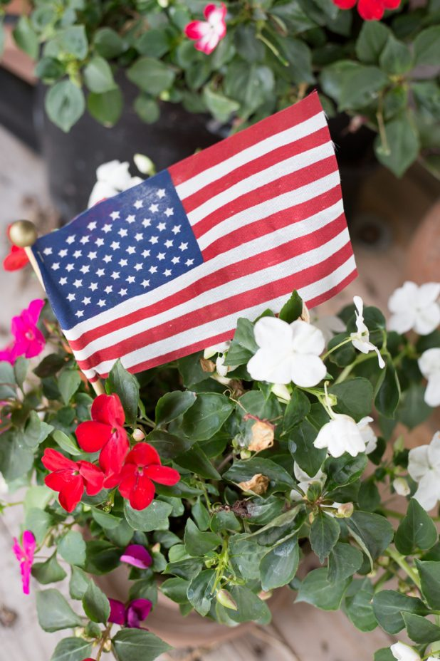 Decorating for the 4th of July by adding simple American flags to my outdoor flower planters