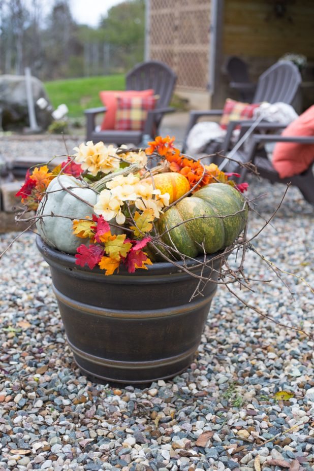 Fall Container Garden Using Pumpkins, Faux Flowers, Branches, and Grapevine