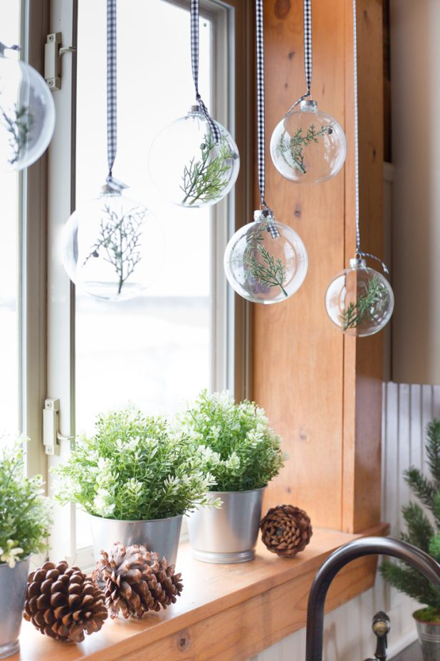DIY Christmas Window Treatment Using Clear Glass Ornaments and Pine Clippings Hung From a Curtain Rod With Ribbon