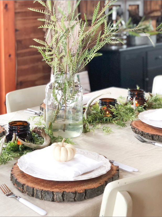 Rustic Natural Thanksgiving Table Using Deer Antlers, Greenery, Wood Slices, Mason Jars, and Natural Colors