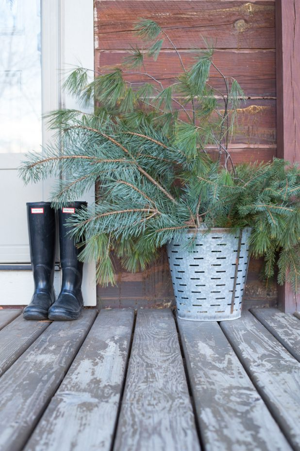 Rustic Winter Porch of a Log Cabin. Hunter Boots, Galvanized Olive Bucket, and Fresh Pine Clippings