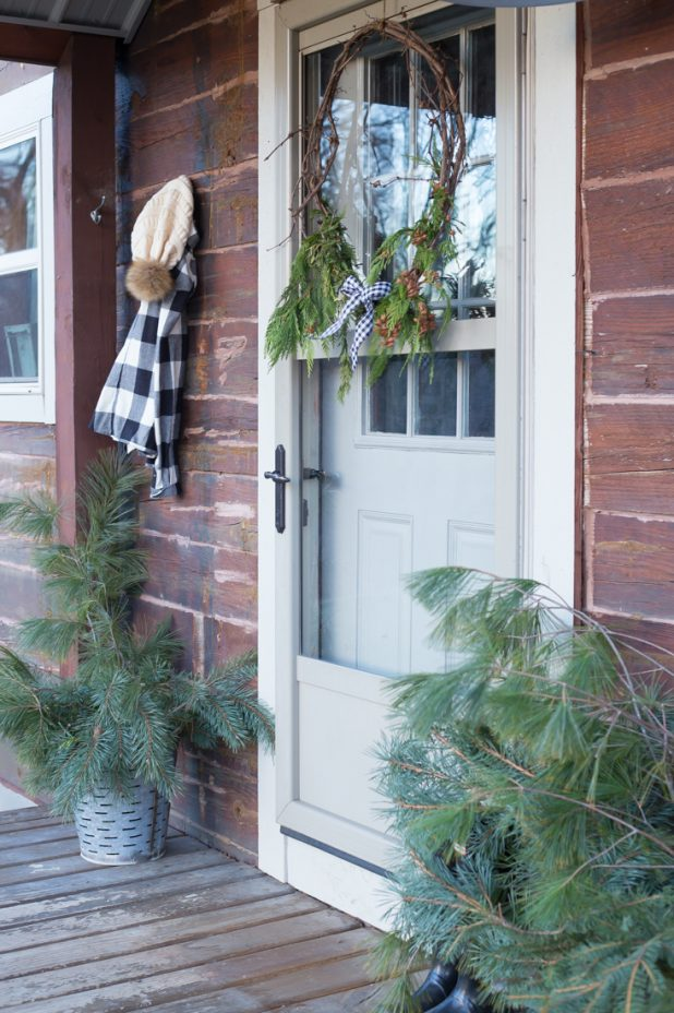 Rustic Winter Christmas Porch, Log Home, Galvanized Olive Bucket, Hunter Boots, Black and White Buffalo Check, Grapevine Wreath, and Pine Clippings