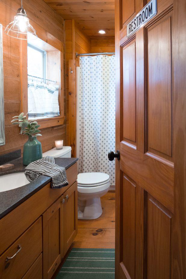 Using a old kitchen farmhouse valance as a bathroom window treatment. Log home, log cabin, farmhouse style, cage lights, black and white gingham, green. Neutral natural decor. Bathroom farmhouse makeover ideas