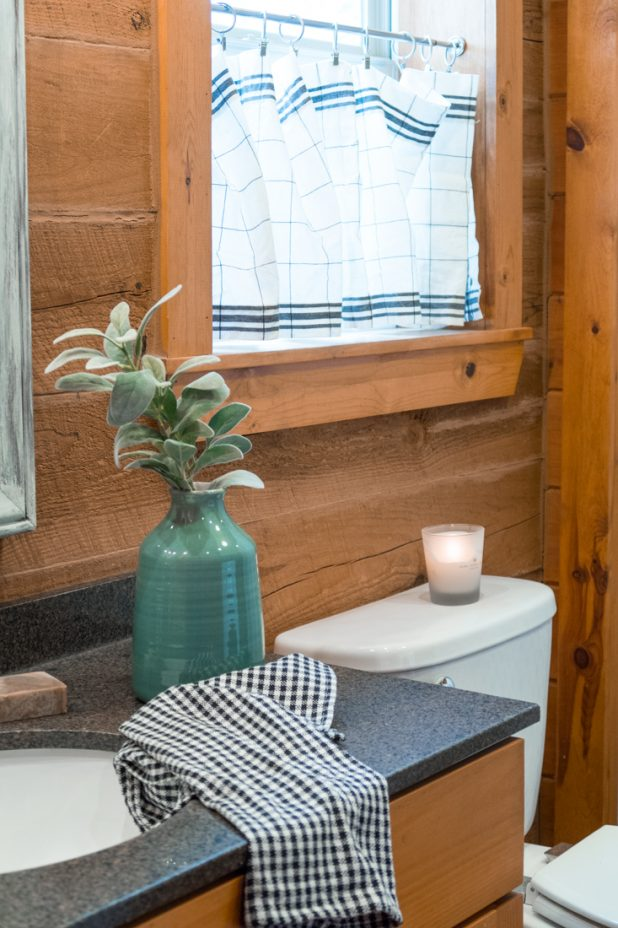 Using a old kitchen farmhouse valance as a bathroom window treatment. Log home, log cabin, farmhouse style, cage lights, black and white gingham, green. Neutral natural decor. Bathroom farmhouse makeover ideas