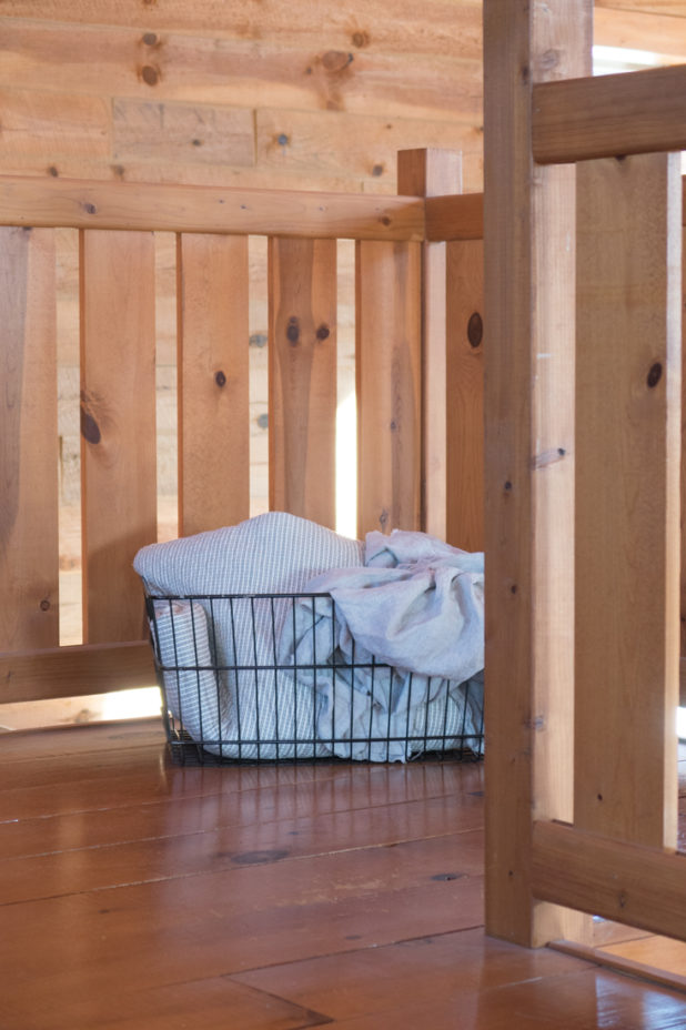 Wire Basket Filled With Linens and Ticking On The Landing of a Log Home