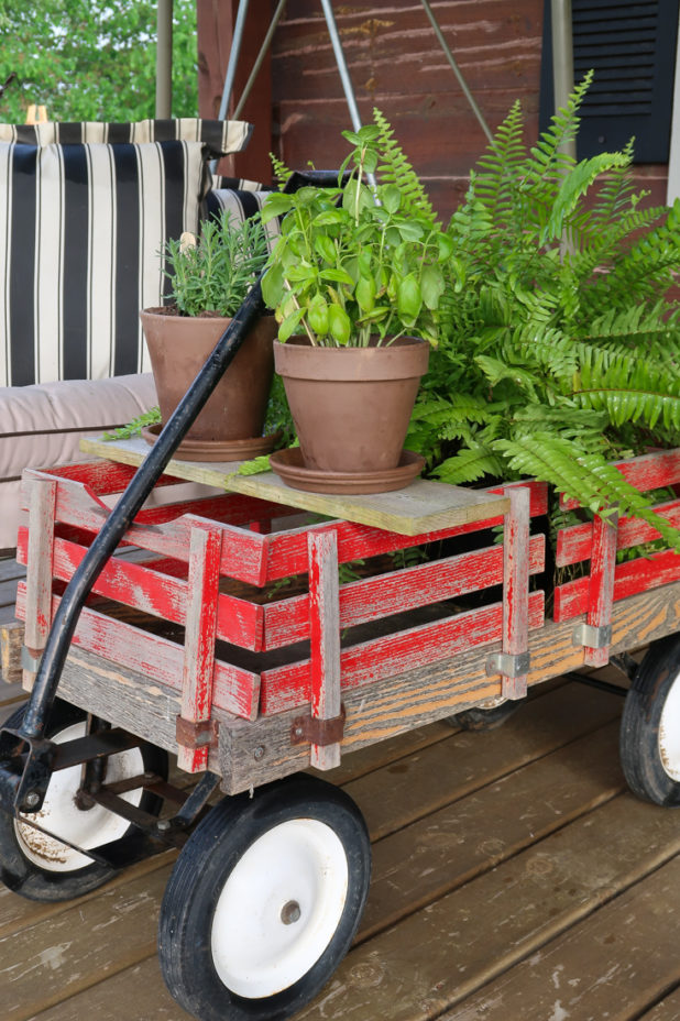 Vintage Red Wagon Used as a Coffee Table to Hold Herbs and Plants On The Covered Porch