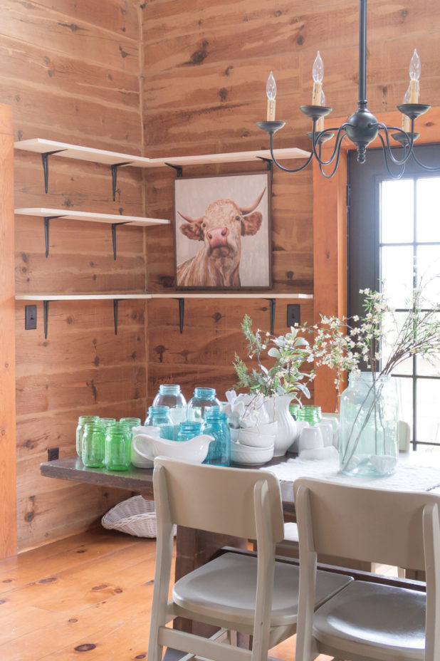 Clearing off the open farmhouse shelves to give them a summer refresh. Using a large cow print, blue and green mason jars, faux greenery, and white dishes to complete the look.