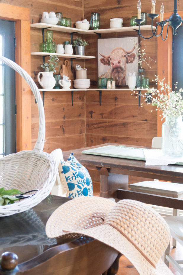 Styling farmhouse shelves with mason jars, white dishes, faux greens, a large cow print, and cutting boards all in a log home dining room.