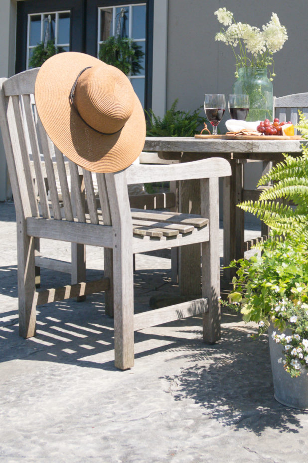 Outside Patio, Teak Furniture, Wildflowers, Straw Hat, Cheese Grapes and Cracker Board, Wine.